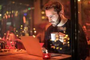 A young man drinking coffee while reading online reviews about long distance movers NJ on his laptop
