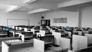 Modern office space - many white desks with computers and headsets.