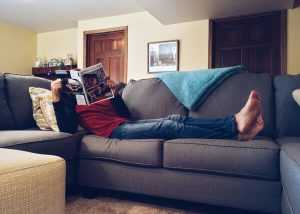A man relaxing on the couch, reading a magazine while local movers NJ do their job
