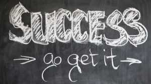 "The words ""SUCCESS - go get it"" written on a black board."