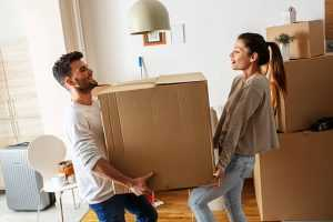 A young man and a young woman in their apartment, holding a big box together