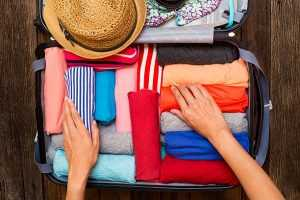 A suitcase full of rolled clothing items and a pair of hands filling the suitcase