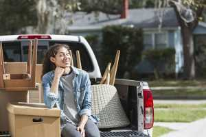 A smiling young woman sitting in the back on a vehicle surrounded by household items