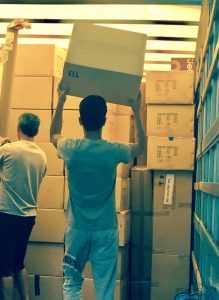 Two male Essex County movers lifting boxes in a storage unit full of boxes