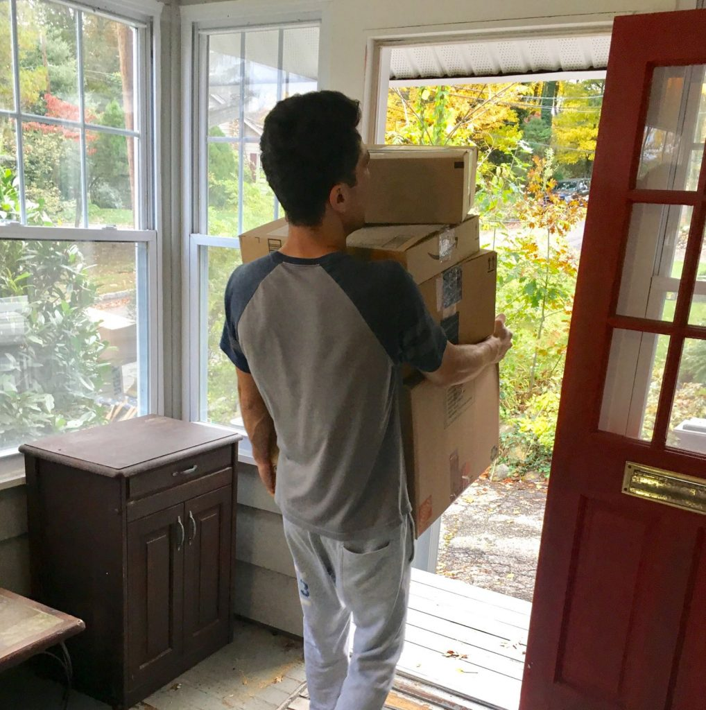 One of qualified Hoboken movers carrying boxes through the front door
