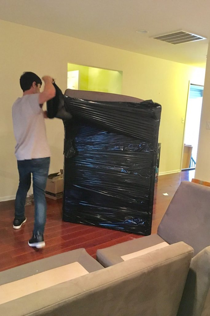 One of our movers Hudson County NJ wrapping a large piece of furniture