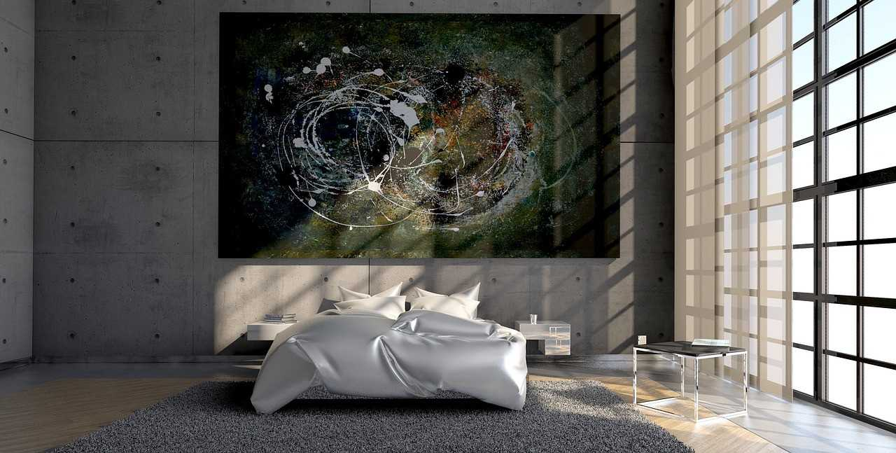A bedroom with a bed, a carpet and a large abstract painting on the wall