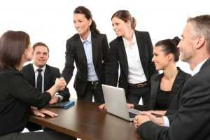 Six smiling business people - your potential colleagues in some of the NJ cities for IT experts