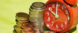A red clock next to a lot of metal coins
