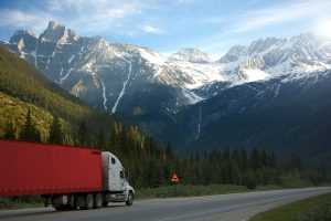 A moving truck marked as cargo on the road, mountains covered with snow in the background