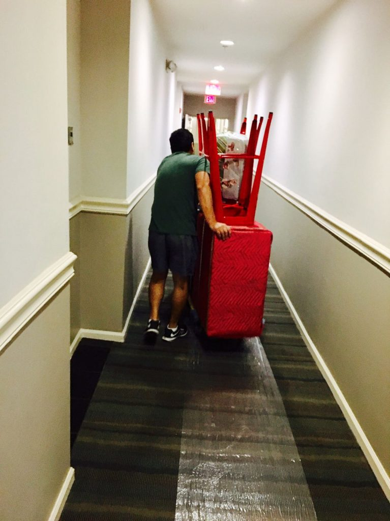 A mover from Bloomfield moving furniture down a narrow hallway