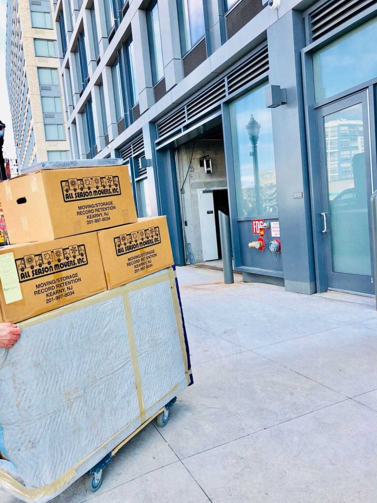 Moving boxes being delivered by movers Union NJ in front of a building