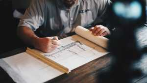 Man looking at a construction plan - keep informed to cope with a neighbor's renovation.
