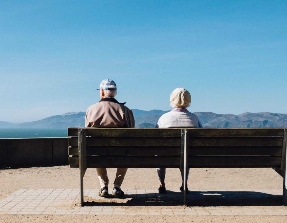 A couple of senior citizens sitting on a bench