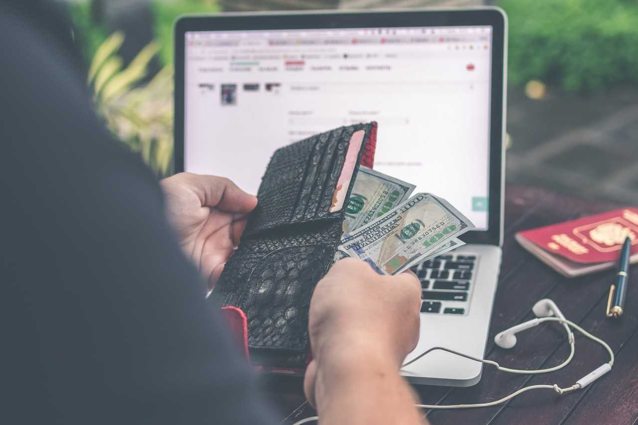 A person taking money from a wallet, a laptop in the background