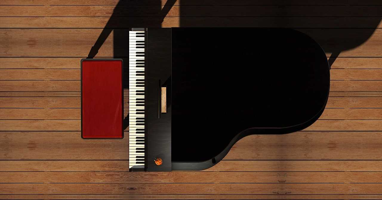 A black piano and a chair on a wooden floor