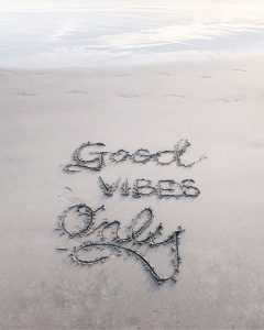 Good vibes only written in sand on a beach