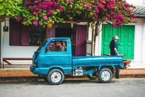 Small blue truck parked in a street