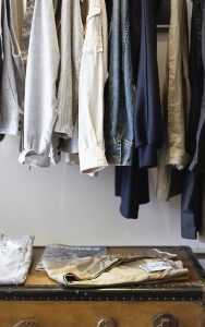 Clothes in a closet, on hangars.