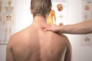 A doctor examining the spine - one of the most common moving injuries.
