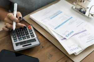 A table, some paper invoices and a female hand using a calculator, calculating the hidden costs of moving