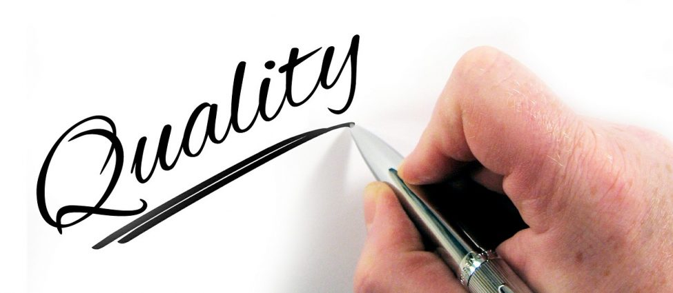 A hand writing the word quality on a white surface