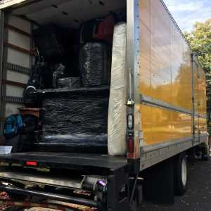 Packing a moving truck in progress - a large truck loaded with packed items