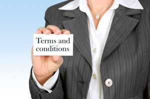 "A woman holding a small card with the words ""Terms and conditions"" on it"