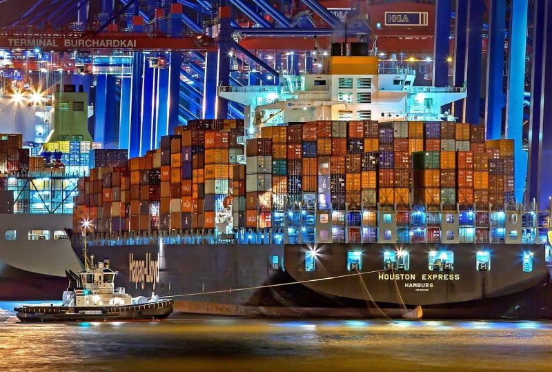 Hamburg port - a large ship full of cargo and a small boat next to it