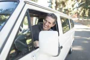 Man smiling while driving car because he has purchased the right type of moving insurance