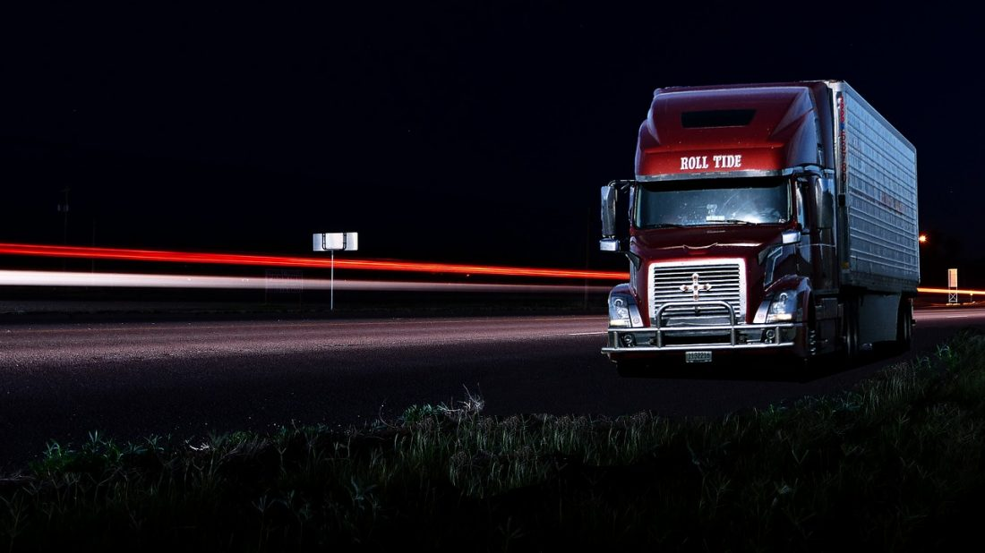A red truck on a highway at night