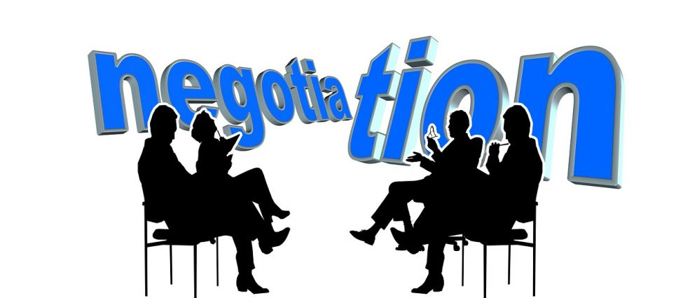 """The word """"negotiation"""" behind the silhouettes of four people sitting with their legs crossed"""